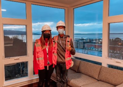 Two People Wearing Construction Hats Inside of an Apartment at Stateside