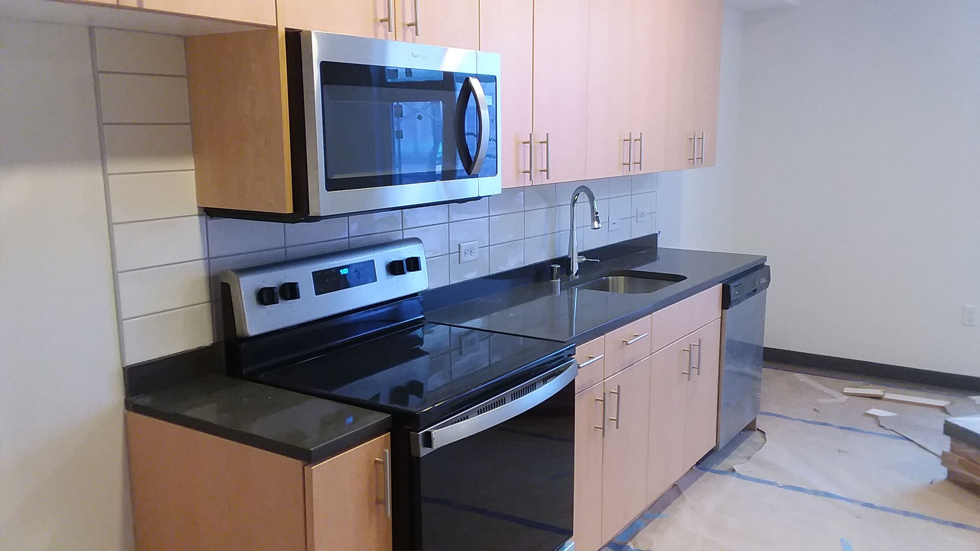 A Stove, Microwave, and Sink in the Kitchen of an Apartment at Stateside